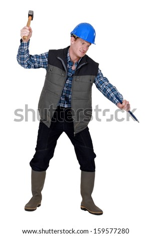 Crazy man using a hammer and chisel - stock photo