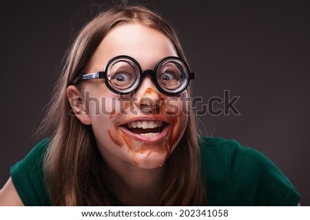 Crazy nerd girl in eyeglasses with ketchup or blood on her face - stock photo