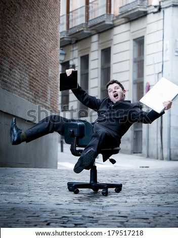 crazy overworked  business man rolling downhill on chair with computer and tablet - stock photo