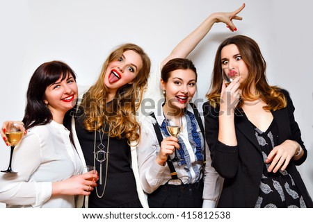 Crazy party image of four pretty woman, having fun at b day celebrating, black and white evening party, glamour clothes hairstyle and make up , funny faces and grimaces. Drinking champagne. - stock photo