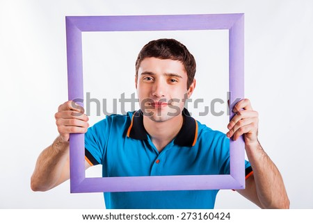 Crazy picture. Handsome young man in shirt holding picture frame in front of his face and smiling while standing against grey background - stock photo