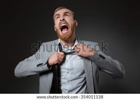 Crazy rage businessman with beard shouting and taking off his tie over grey background - stock photo