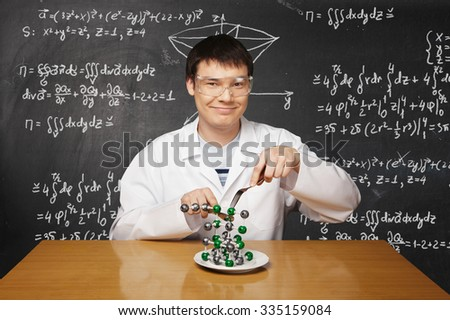 Crazy scientist eats atom with fork and knife. Creative concept. - stock photo