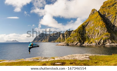 Crazy tourist jumping on the coast of fjord with stunning mountains on Lofoten islands in Norway - stock photo