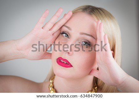 Crazy woman blonde holds her hands on  head.  Isolated on grey background.