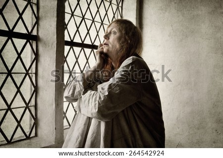 Crazy woman by the window of a medieval asylum - stock photo