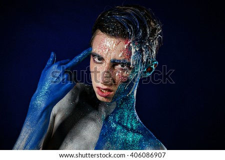 Crazy young androgyne man with face art. Freak person. Sperm on face. Tinsel creative blue makeup. Intersex and homosexuality concept. Space for logo