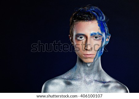 Crazy young androgyne man with face art. SPACEMAN. Freak person. Sperm on face. Tinsel creative blue makeup. Intersex and anorexia concept. Space for logo