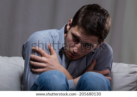 Crazy young desperate man sitting on the sofa in the dark - stock photo