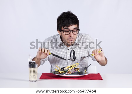 Crazy young man eating technology at his dinner plate - stock photo