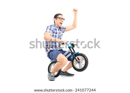 Crazy young man riding a small bike isolated on white background - stock photo