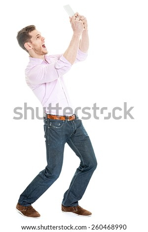 Crazy young man screaming at tablet pc - stock photo