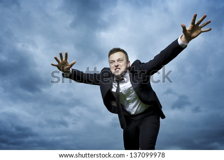 Crazy young man throws himself in front of him to attack. I want to catch something. He is furious and determined to reach your goal. - stock photo