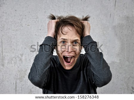 Crazy young man with the face of despair - stock photo