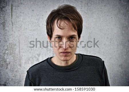 Crazy young man with the face of evil - stock photo