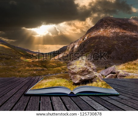 Creaive concept image of sunset over mountain range in pages of book - stock photo