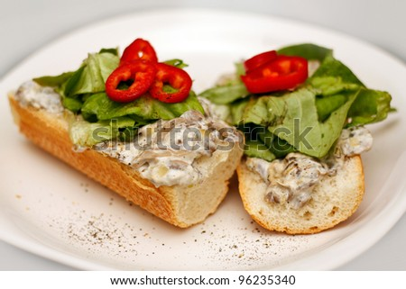 Cream and mushroom sandwiches served on a plate with paprika, pepper and green salad