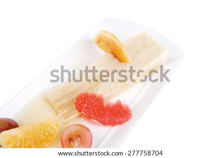cream cake and fruits served on white plate