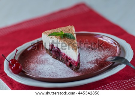 cream cake with a cherry on a white plate and red - stock photo