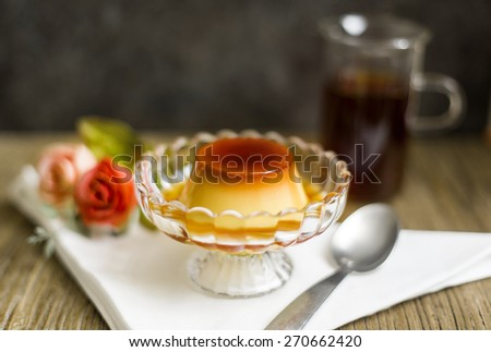 Cream caramel dessert served in clear glass bowl on white napkin with black tea - stock photo