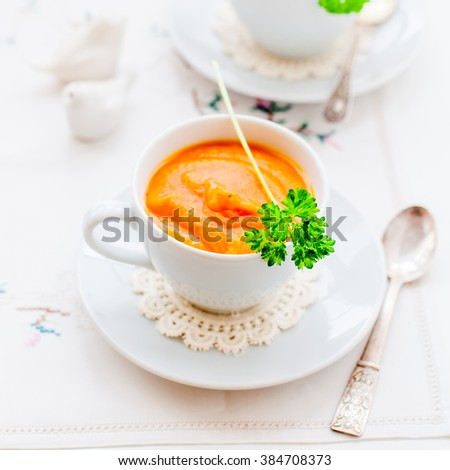 Cream Carrot Soup in a White Cup Garnished with a Parsley Leaf, square