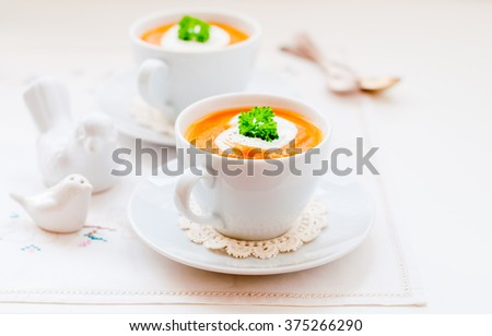 Cream Carrot Soup in a White Cup Garnished with Sour Cream and a Parsley Leaf, copy space for your text - stock photo