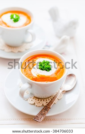 Cream Carrot Soup in a White Cup Garnished with Sour Cream and a Parsley Leaf, copy space for your text
