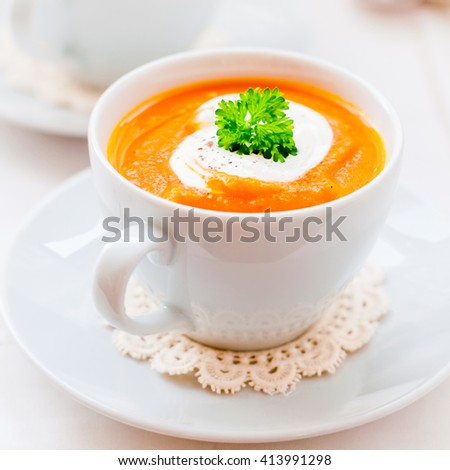 Cream Carrot Soup in a White Cup Garnished with Sour Cream and a Parsley Leaf, square - stock photo