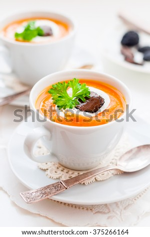 Cream Carrot Soup in a White Cup Garnished with Sour Cream, Truffle Slices and a Parsley Leaf, copy space for your text - stock photo