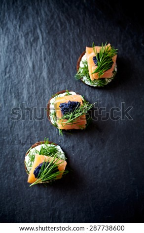 Cream cheese, smoked salmon and caviar on pumpernickel - stock photo