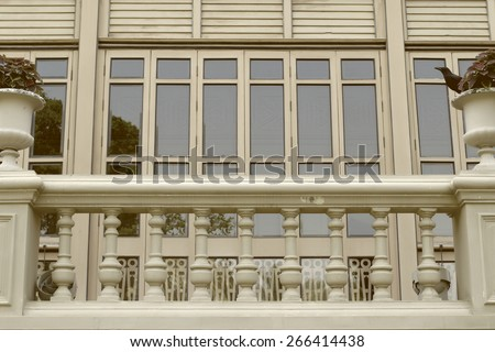 Cream colored wooden houses with balconies and planter - stock photo