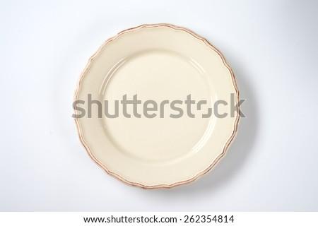cream decorative plate on white background - stock photo