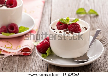 Cream dessert with raspberries in small cups - stock photo