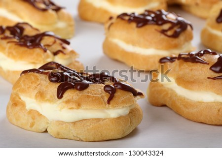 Cream filled eclair with chocolate icing on baking sheet