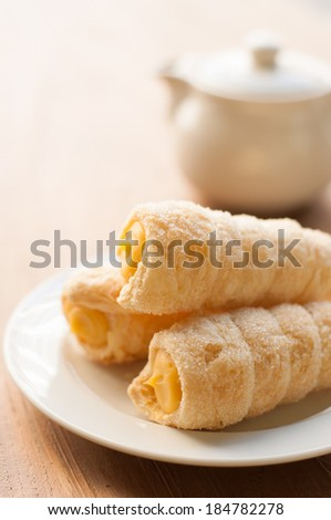 Cream-filled pastry roll on the wood board