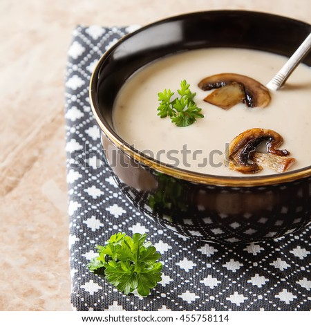 Cream homemade mushroom soup in a black plate, parsley. Marble table - stock photo
