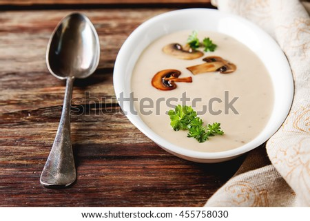 Cream homemade mushroom soup in a white plate with parsley.  - stock photo