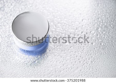 Cream jar on water drop silver table.Concept cool and fresh. - stock photo
