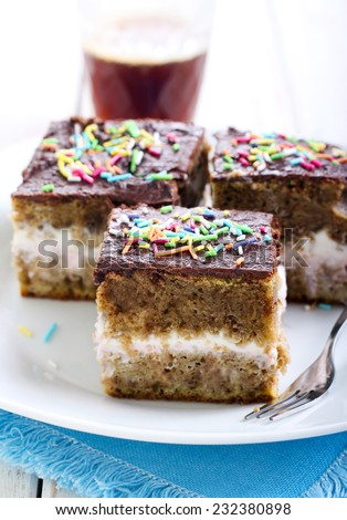 Cream layered cake with chocolate icing and sprinkles - stock photo
