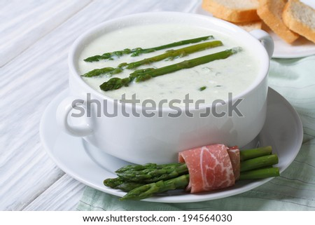 Cream of asparagus soup close-up in white plate. horizontal  - stock photo
