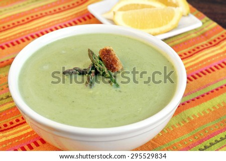 Cream of asparagus soup garnished with asparagus tips and a crouton.