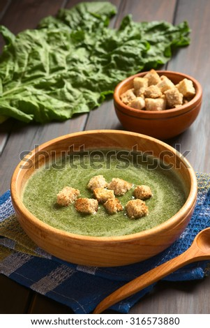 Cream of chard soup with croutons in wooden bowl, fresh raw chard leaves, bowl of croutons in the back, photographed on dark wood with natural light (Selective Focus, Focus on the first croutons) - stock photo