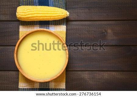 Cream of corn soup in wooden bowl with corn cob on towel, photographed overhead on dark wood with natural light - stock photo