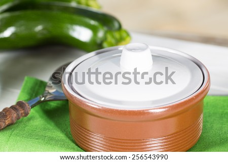 Cream of fresh zucchini in a clay pot - stock photo