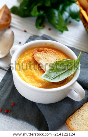 Cream of pumpkin soup with basil leaves, in a bowl - stock photo