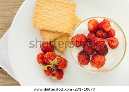 Cream pudding with strawberry in glass and crackers horizontal selective focus top view - stock photo