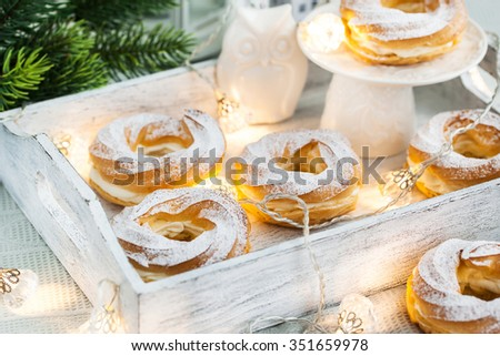 Cream puff rings (choux pastry) on white christmas background - stock photo