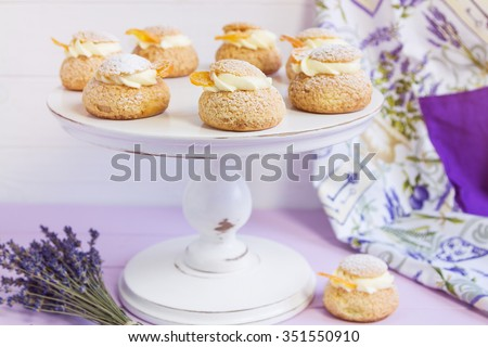 Cream puffs filled vanilla cream and slice of orange, dusted with  icing sugar on white cake stand - stock photo