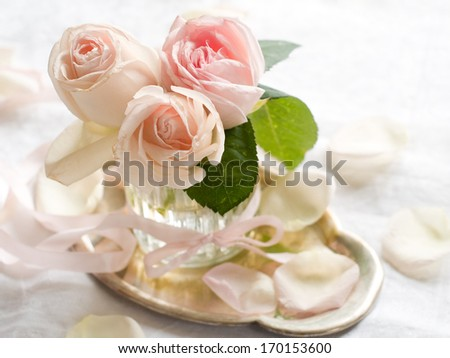 Cream roses in vintage glass vase for celebration, selective focus
