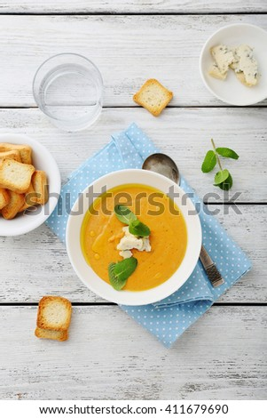 cream soup in bowl on wooden table, food top view - stock photo
